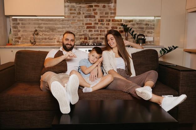 Tata, syn i mama oglądają telewizję na kanapie w mieszkaniu. rodzina spędza szczęśliwy wieczór w domu. uśmiecha się młoda matka z długimi włosami.