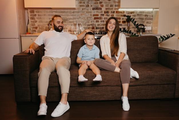 Tata, syn i mama oglądają telewizję na kanapie w mieszkaniu. szczęśliwa rodzina cieszy się wieczorem. krewni w domu. śmieje się młoda matka z długimi włosami.