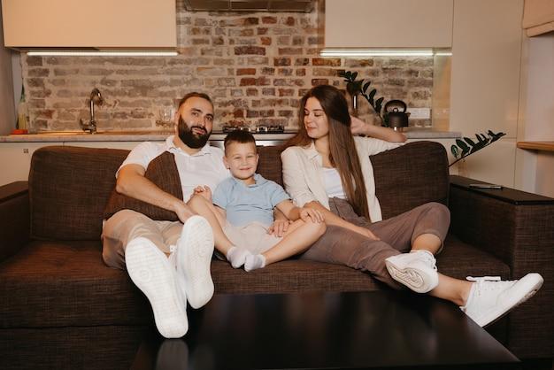 Tata, syn i mama oglądają telewizję na sofie w mieszkaniu