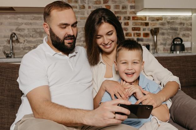 Tata, syn i mama oglądają wideo na kanapie. szczęśliwy mąż z brodą pokazuje wieczorem w domu na smartfonie śmiejącemu się dziecku i żonie.