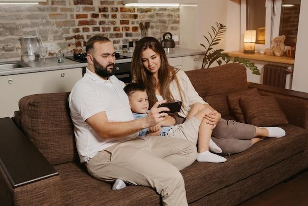 Tata, syn i mama oglądają wideo na smartfonie na kanapie. ojciec z brodą demonstruje wieczorem wiadomościom rodzinnym na ekranie telefonu komórkowego w domu.