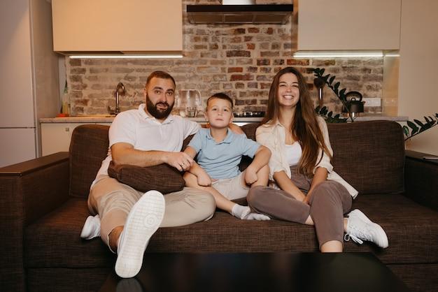 Tata, syn i mama z zainteresowaniem oglądają telewizję na kanapie w mieszkaniu. rodzina spędza szczęśliwy wieczór w domu. młoda matka z długimi włosami uśmiecha się.