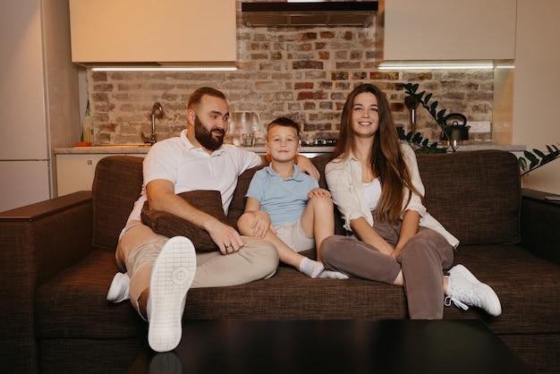 Tata, syn i mama z zainteresowaniem oglądają telewizję na kanapie w mieszkaniu. rodzina spędza szczęśliwy wieczór w domu. ojciec wpatruje się w swojego chłopca i żonę.