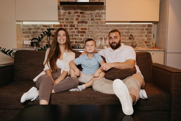 Tata, syn i mama z zainteresowaniem oglądają telewizję na sofie w mieszkaniu