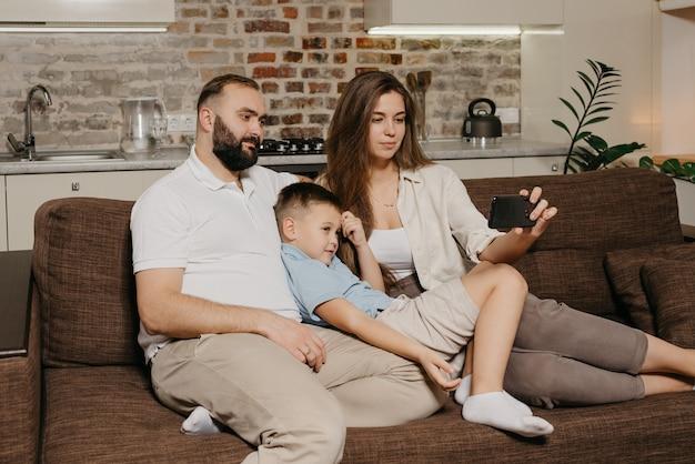 Tata, syn i młoda mama oglądają wideo na smartfonie na kanapie. mama z długimi włosami demonstruje wieczornym wiadomościom rodzinnym na ekranie telefonu komórkowego wieczorem w domu.