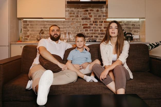 Tata, syn i młoda mama z długimi włosami z zainteresowaniem oglądają telewizję na kanapie w mieszkaniu. rodzina spędza szczęśliwy wieczór w domu.