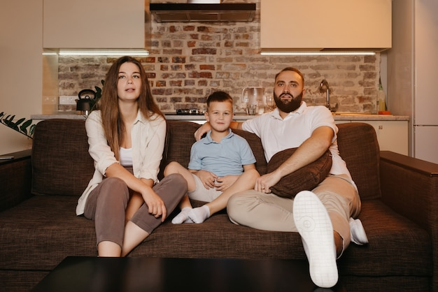 Tata, syn i młoda mama z długimi włosami z zainteresowaniem oglądają telewizję na sofie w mieszkaniu