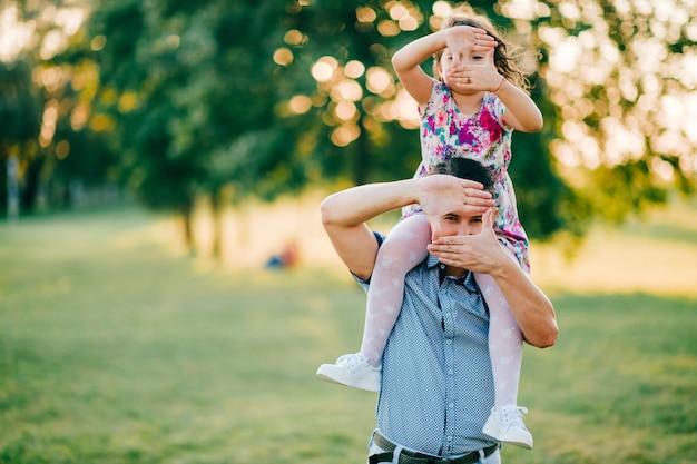 Tata trzyma córkę na ramionach w przyrodzie.