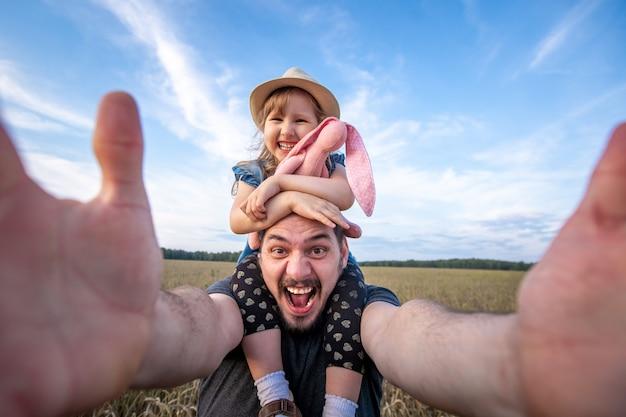 Tata trzyma córkę na ramionach.