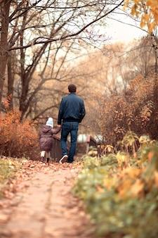Tata trzyma córki za rękę szczęśliwa rodzina spaceruje jesienią parkhello wrzesień