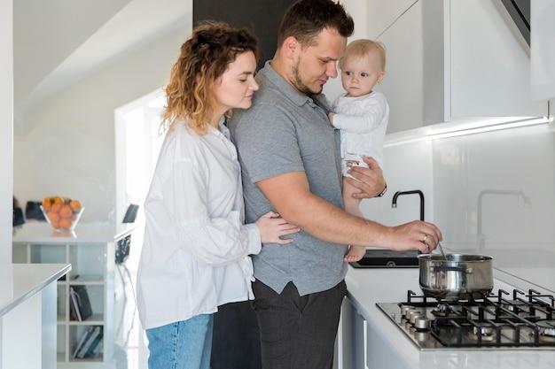 Tata trzyma dziecko i gotuje