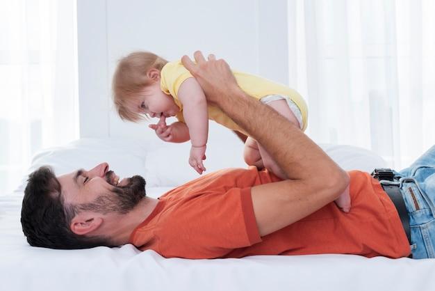 Tata trzyma dziecko i uśmiecha się