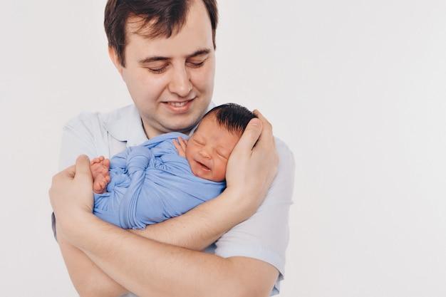 Tata trzyma dziecko w ramionach