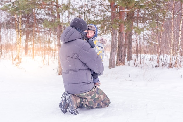 Tata trzyma i przytula swojego synka w zaśnieżonym lesie lub w zimowym parku. koncepcja zimowych zajęć na świeżym powietrzu dla rodziny.