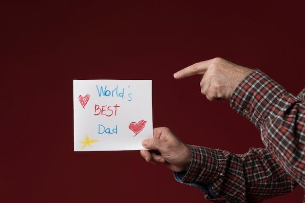 Tata trzyma kartkę z życzeniami dzień ojca