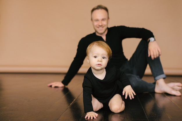Tata trzyma roczną córkę na beżowym tle. ojcowska miłość. dzień ojca