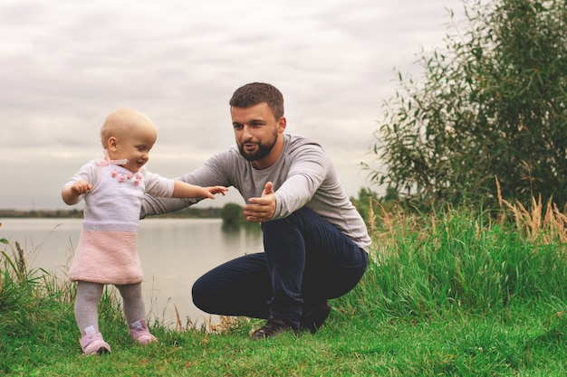 Tata uczy córkę chodzenia, parkowania, przyrody. chodzić po trawie. ojciec i córka. pierwsze kroki.