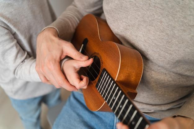 Tata uczy swoją córkę gry na ukulele. domowe nauczanie gry na gitarze. zbliżenie na struny ukulele i ręce.