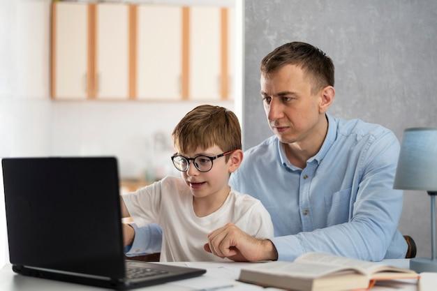 Tata uczy syna pracy z programem komputerowym. tata pomaga synowi odrabiać lekcje. nauka online, nauka na odległość