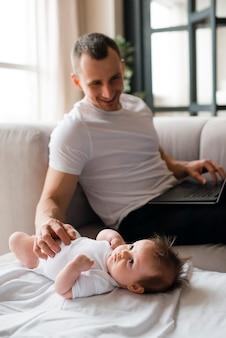 Tata używa laptop i wzruszającego dziecka lying on the beach na koc