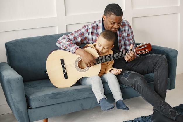 Tata w kraciastej koszuli. mały synek trzyma gitarę. ojciec i syn siedzi na kanapie.