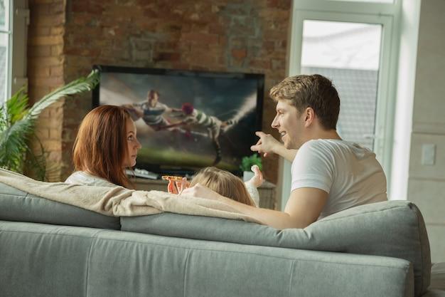 Tata wybiera kanał. rodzina spędzająca miło czas razem w domu. mama, tata i córka bawią się, jedzą pizzę, oglądają w telewizji mistrzostwa rugby. razem, komfort w domu, koncepcja miłości.