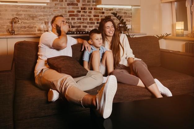 Tata z brodą, syn i młoda mama z długimi włosami oglądają telewizję na sofie