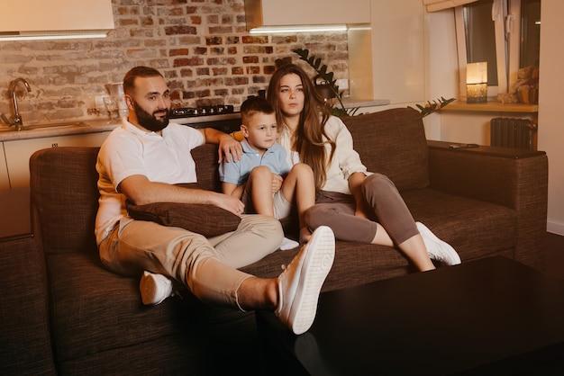 Tata z brodą, syn i młoda mama z długimi włosami uważnie oglądają telewizję na kanapie. rodzina spędza szczęśliwy wieczór w domu.