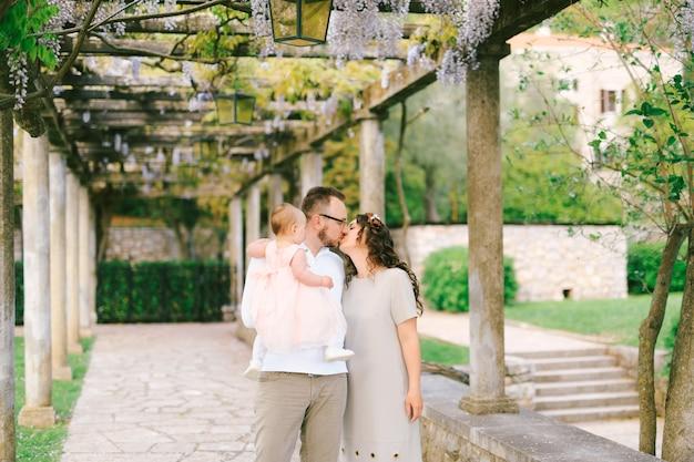 Tata z córeczką w ramionach całuje mamę w alejce z kwitnącymi kolumnami glicynii i