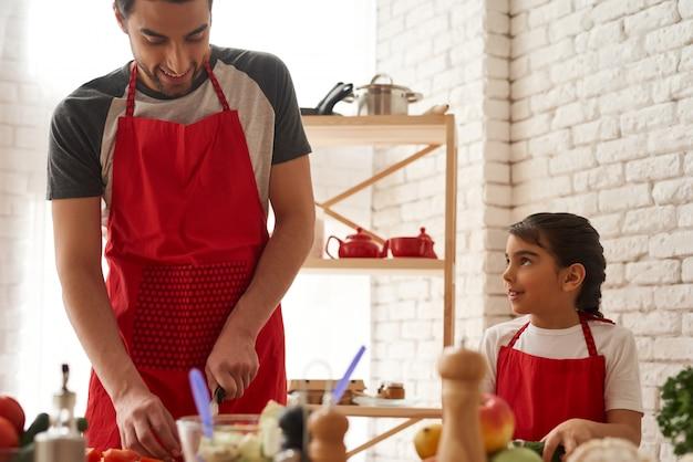 Tata z córką cięcia warzyw w kuchni.