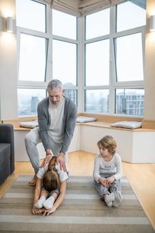 Tata z dziećmi robi poranną rozgrzewkę na podłodze