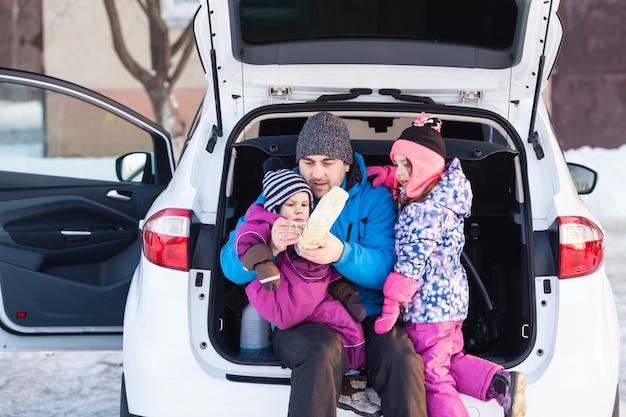 Tata z dziećmi siedzą w bagażniku samochodu i przygotowują się do jazdy na nartach