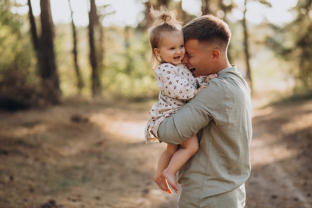 Tata z małą córeczką przytulanie w lesie