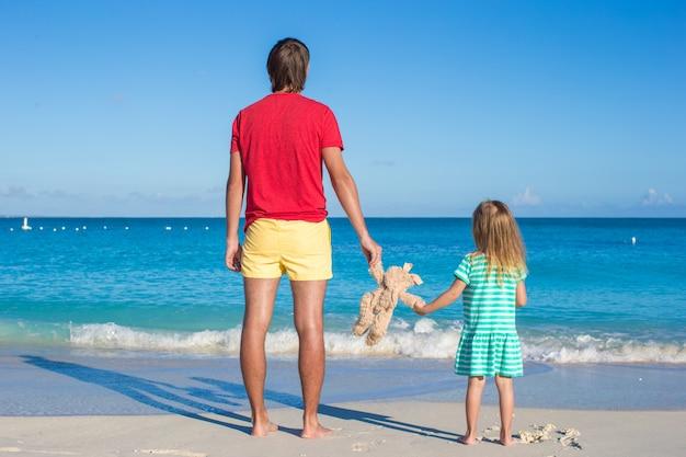 Tata z małym dzieckiem trzymającym pluszową zabawkę na egzotycznej plaży