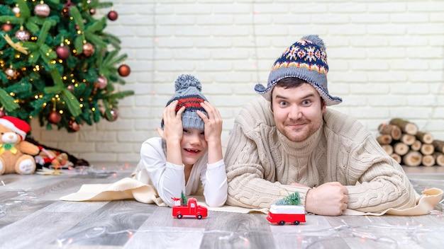 Tata z synem bawią się na podłodze przy choince w domu. szczęśliwy pomysł rodzinny