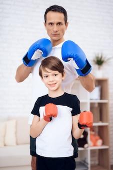 Tata z synem w rękawiczkach pozuje dla kamery.