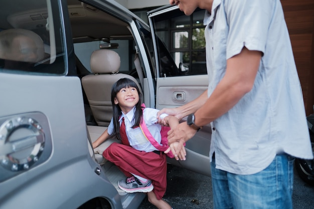 Tata zabiera córkę rano do szkoły jadąc samochodem