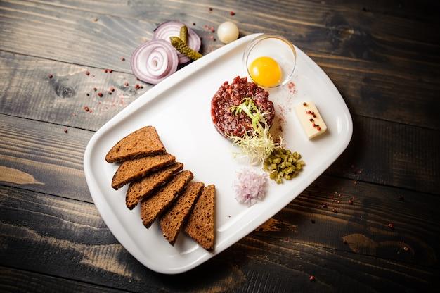 Tatar wołowy z marynowanym ogórkiem i świeżą cebulą.