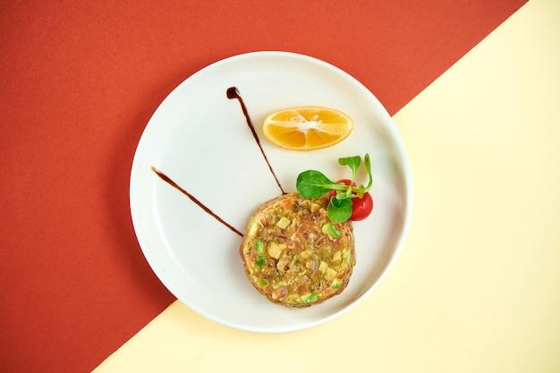 Tatar z łososia z awokado i cytryną w białym talerzu na kolorowej powierzchni.