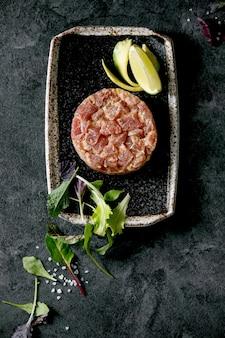 Tatar z tuńczyka z zieloną sałatą, limonką, awokado i sosem musztardowym na czarnym talerzu ceramicznym w stylu japońskim na tle z czarnego marmuru. leżał na płasko, miejsce na kopię. przystawka do restauracji