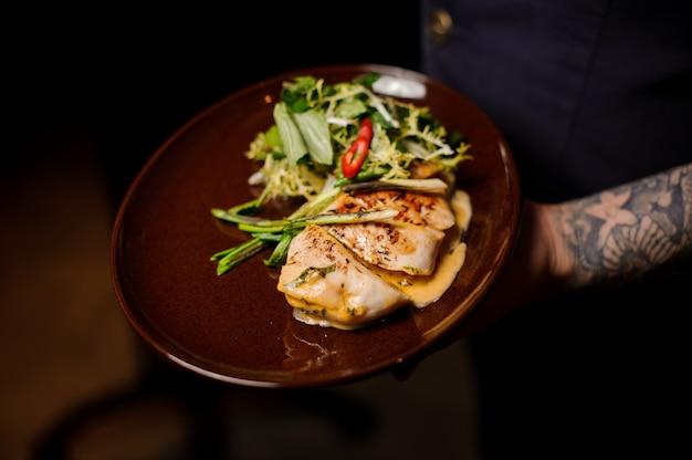Tattoed barman trzyma talerz fileta z kurczaka i sałatki