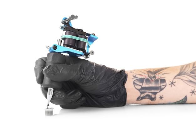 Tattooist ręka w czarnej rękawiczce z maszyną do tatuażu na białym tle, z bliska
