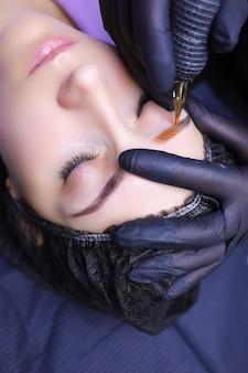 Tatuator nakłada szkic pomarańczowego pigmentu klienta za pomocą maszynki do tatuażu