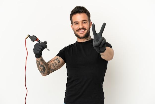 Tatuażysta mężczyzna na białym tle uśmiechający się i pokazujący znak zwycięstwa