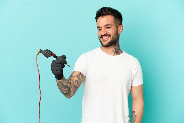 Tatuażysta mężczyzna na odosobnionym niebieskim tle ze szczęśliwym wyrazem