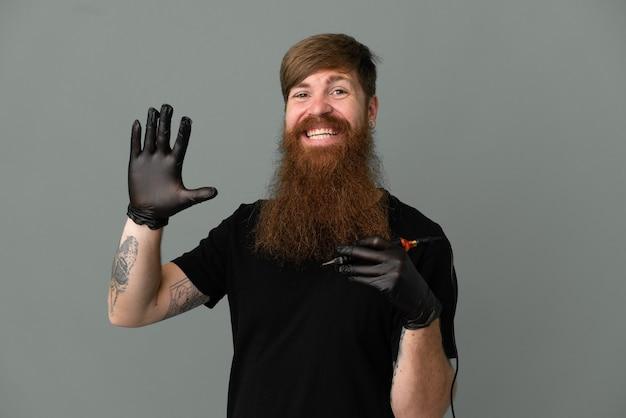 Tatuażysta rudy mężczyzna na białym tle na niebieskim tle pozdrawiając ręką ze szczęśliwym wyrazem