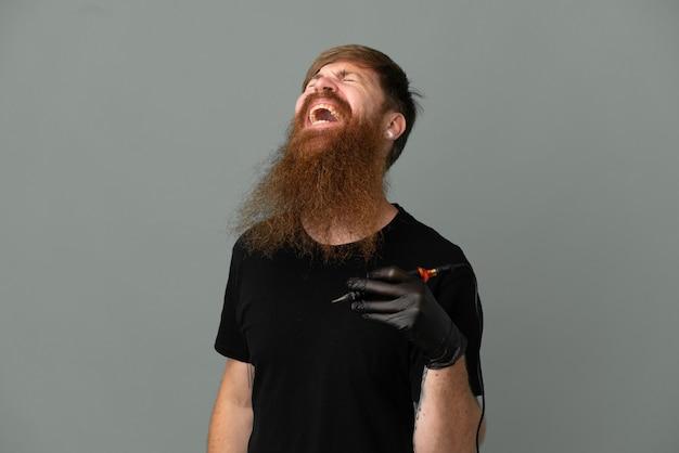 Tatuażysta rudy mężczyzna na białym tle na niebieskim tle śmiejąc się