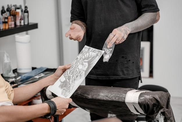 Tatuażysta w salonie rysuje piękny szkic tatuażu byka na papierze długopisem dla swojego klienta i pokazuje go.