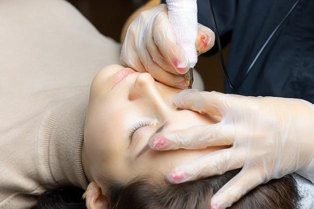 Tatuażysta w trakcie pracy nad trwałym makijażem powiek