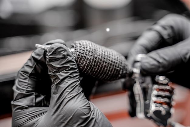 Tatuażysta z bliska w czarnych rękawiczkach przygotowuje maszynkę do tatuażu do pracy w nowoczesnym studio tatuażu.
